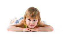 Cute little girl lie on the floor. Studio shot royalty free stock photo