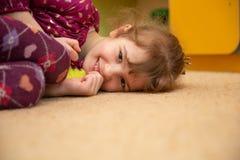 Cute little girl lie on the floor. Studio shot. Cute little girl smile and lie on the floor in the kindergarten. girl dreams. Copy space stock photography