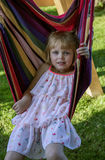 Cute little girl lies in a hammock outdoors, has a rest in the garden. Stock Image