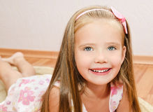 Cute little girl lies on a house floor Stock Images