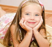 Cute little girl lies on a house floor Royalty Free Stock Photos