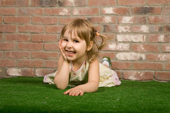 Cute little girl lies and smiles Royalty Free Stock Images