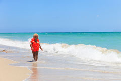 Cute little girl in life jacket on summer beach, safety Stock Photos