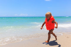 Cute little girl in life jacket on summer beach, safety Royalty Free Stock Photo