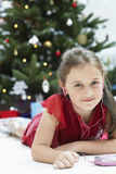 Cute Little Girl Listening Music Through Cd Payer. Portrait of cute little girl listening music through CD payer with Christmas tree in background Royalty Free Stock Photos