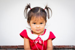 Cute little girl is listening music on earphones Stock Photos