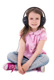 Cute little girl listening music in headphones isolated on white Royalty Free Stock Image