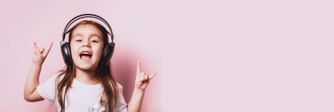 Cute little girl listening music wearing headphones. On pink background. Funny emotions. Copyspace for text stock photo