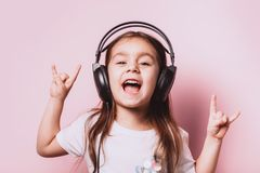 Cute little girl listening music wearing headphones. Cute little girl listening music wearing headphones on pink background. Funny emotions. Copyspace for text stock photos