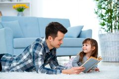 Cute little girl listening to dad reading fairy tale lying on warm floor together, caring father holding book , family hobbies royalty free stock photography