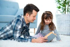 Cute little girl listening to dad reading fairy tale lying on warm floor together, caring father holding book , family hobbies stock image