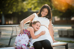 Cute little girl listening to her mothers belly and laughing Royalty Free Stock Photography