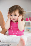 Cute little girl listening to music on bed Royalty Free Stock Photos