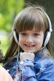 Cute little girl listening to music and enjoying the park. Beautiful little girl listens to music and enjoying the park Stock Photos