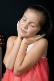 A cute little girl listening to music with headphones. A cute little girl listening to music with black headphones Royalty Free Stock Image