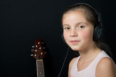 A cute little girl listening to music with headphones. A cute little girl listening to music with black headphones Stock Photo