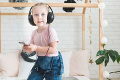 Cute little girl listening to music on headphones at home. stock photos