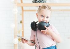 Cute little girl listening to music on headphones at home. stock photography