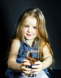 Cute little girl with long hair holding glass of water Stock Images
