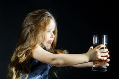 Cute little girl with long hair holding glass of water Stock Image