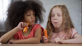 Free Cute Little Girl Looking At Friend Eating Carrots With Appetite, Healthy Food Stock Photography - 132349102