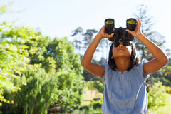 Cute little girl looking through binoculars. On a sunny day stock photography