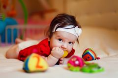 Adorable girl on the bed. Cute little girl looking at camera and crawling on the bed at home royalty free stock photo