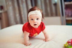 Adorable girl on the bed. Cute little girl looking at camera and crawling on the bed at home stock photo
