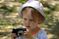 Cute little girl looking at the camera screen. Summer. On a walk stock images
