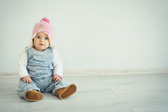 A cute little girl is looking into the camera and is wearing a pink knitted hat. Blue eyes kid. Stock Photography