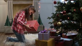 Cute little girl looking for gifts under Xmas tree stock video footage