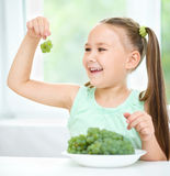 Cute little girl is looking at green grapes Royalty Free Stock Images
