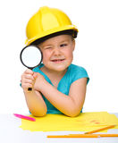 Cute little girl is looking through magnifier Stock Images