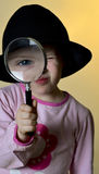 Cute, little girl looking through a magnifying glass Royalty Free Stock Photos