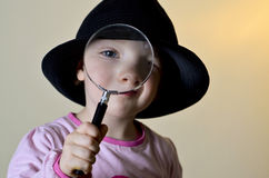 Cute, little girl looking through a magnifying glass Stock Photo