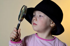 Cute, little girl looking through a magnifying glass Royalty Free Stock Photography