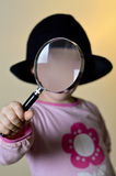 Cute, little girl looking through a magnifying glass Stock Photos