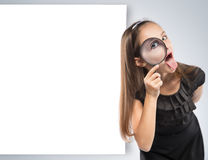 Cute  little girl looking through a magnifying glass. Educational concept Stock Image