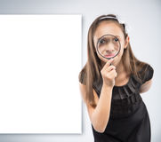 Cute  little girl looking through a magnifying glass. Educational concept Royalty Free Stock Images