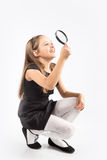 Cute little girl looking through a magnifying glass - isolated on white. Stock Images