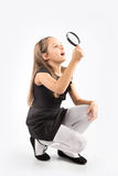 Cute little girl looking through a magnifying glass - isolated on white. Royalty Free Stock Images