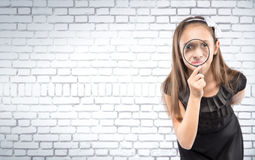 Cute  little girl looking through a magnifying glass white brick wall background. Educational concept Royalty Free Stock Photos