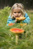 Cute little girl looking at mushrooms in summer - autumn forest Stock Image