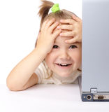 Cute little girl is looking out from her laptop Royalty Free Stock Photos