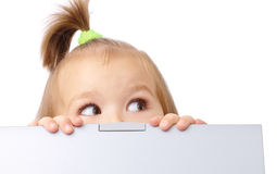 Cute little girl is looking out from her laptop Stock Images
