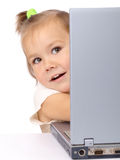 Cute little girl is looking out from her laptop Royalty Free Stock Photo