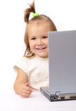Cute little girl is looking out from her laptop Stock Photography