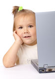 Cute little girl is looking out from her laptop Stock Photos