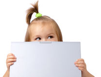 Cute little girl is looking out from her laptop. Isolated over white Stock Photo