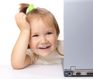 Cute little girl is looking out from her laptop Royalty Free Stock Images